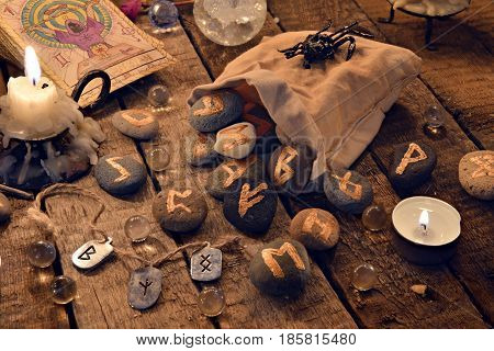 Still life with ancient runes and the tarot cards in candle light. Halloween background, black magic rite or spell, occult and esoteric objects on witch table