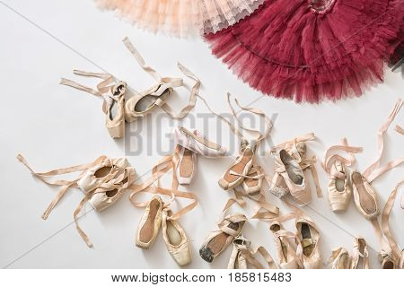 Peach and burgundy tutus and many beige pointe shoes on the light floor in the studio. Top view photo. Closeup. Horizontal.