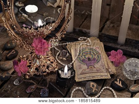 Close up with the tarot cards, mirror and black candle. Halloween background, black magic rite or spell, occult and esoteric objects on witch table