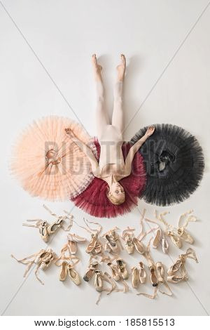 Charming ballerina lies on the colorful tutus on the white floor in the studio. She wears light dance wear. Below her there are many pointe shoes. Tutus are peach, burgundy and black. Top view photo.