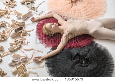 Sensual ballerina lies on the colorful tutus on the white floor in the studio. She wears a light dance wear. On the left there are many pointe shoes. Tutus are peach, burgundy and black. Closeup.