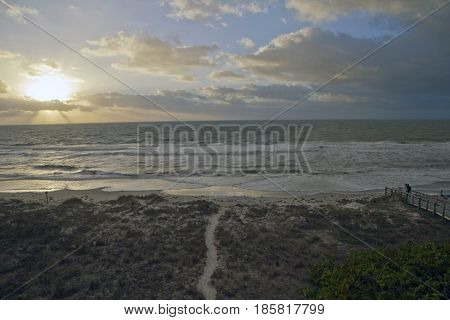 Indian Rocks Florida USA - January 27 2017: A scenic sunset over the Gulf of Mexico at Indian Rocks Beach Florida provides a cloudscape extravaganza for tourists in winter