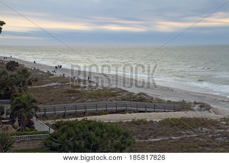 Indian Rocks Florida USA - January 27 2017: Early morning view of Indian Rocks Beach and the Gulf of Mexico with boardwalks leading to a beach where tourists walk in winter on January 27 2017 in Indian Rocks Florida