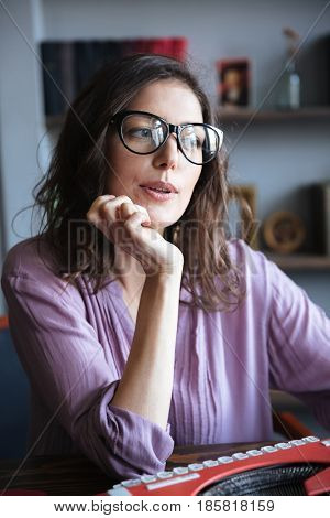 Portrait of a pensive mature authoress in eyeglasses thinking and looking away indoors