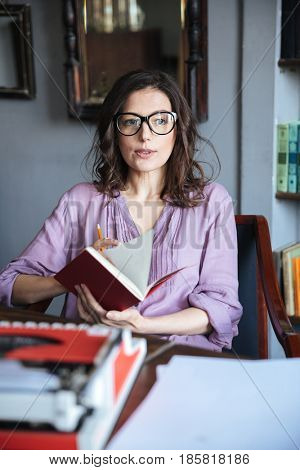 Portrait of a thoughtful mature woman in eyeglasses holding notebook and looking away while sitting at the table indoors