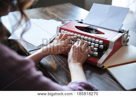Close up portrait of an authoress sitting at the table and typing on typerwriter indoors