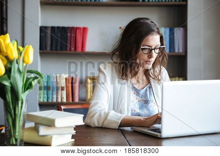 Portrait of a concentrated mature business woman working on a laptop while sitting at the table at home