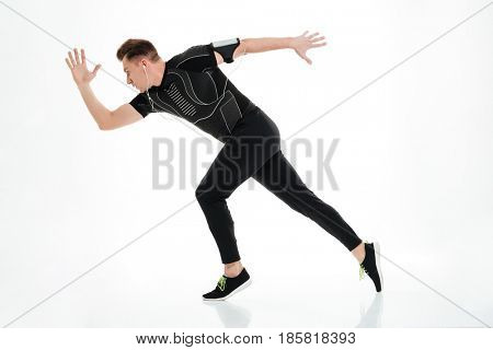 Side view full length portrait of a healthy sportsman started to run isolated over white background