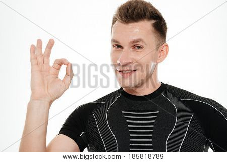 Close up portrait of a smiling strong athlete man showing ok gesture and looking at camera isolated over white background