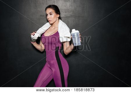 Portrait of a sporty young woman in tracksuit with towel and water bottle isolated over black background