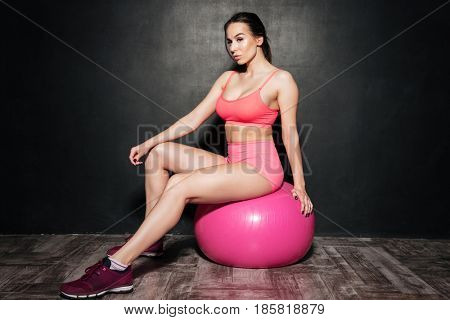 Photo of strong sportswoman sitting over grey background on ball. Looking aside.