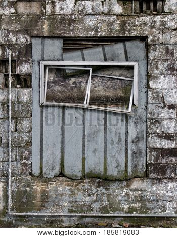 A dilapidated window on a brick building.
