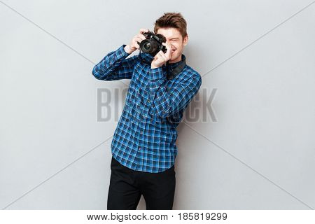 Young man with camera making photo isolated over grey