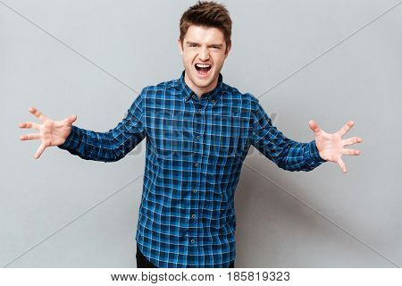 Angry young man screaming at camera and gesturing hands isolated