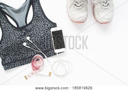 Flat lay of smartphone with measuring tape sport bra and sport shoes on white background with copy space Healthy lifestyle and diet concept