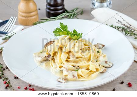 Fettuccine with white mushrooms on white plate