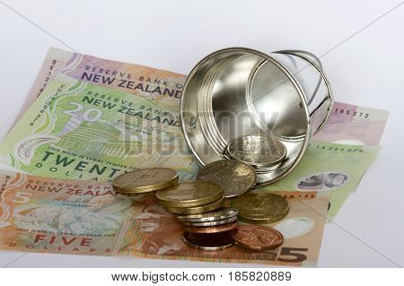New Zealand dollars and cents spilt from a bucket.
