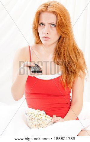 Portrait of beautiful girl watching movie or tv in bed and eating popcorn