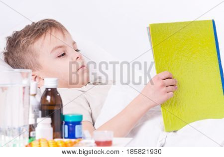 Sick child boy lying in bed with fever, resting at home. Illness kid reading book.