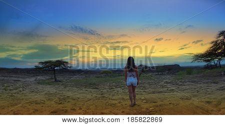 Lonely woman back watching the sunset in the Desierto de la Tatacoa (Tatacoa Desert) in Villavieja, Huila / Colombia