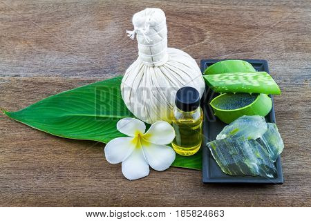 Slice Aloe Vera (Aloe barbadensis Mill.Star cactus Aloin Jafferabad or Barbados) Spa compressing ball and Aloe vera essential oil in green leaf on wooden