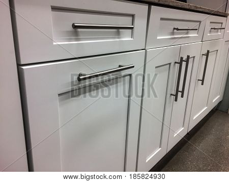 White kitchen cabinets, modern cabinets with stainless steel handles, modern cabinets, white kitchen cabinets, doors and drawers of white kitchen cabinet, wooden cabinetry