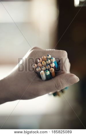 Hand of human holding many pencils. Close-up photo