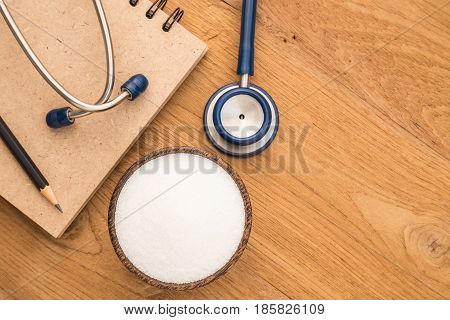 Blue Stethoscope, Sugar And Note Book On Wooden Plank Background. Use For Diabetes Check Up Concept