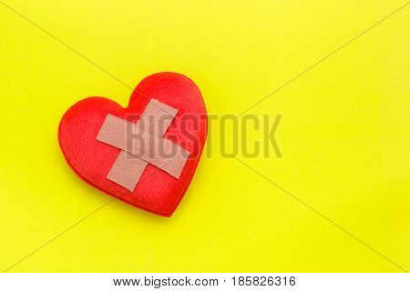 Plaster Or Band-aid On Red Heart Shape On Yellow Background. Use For Heart Problem Or Illness Concep