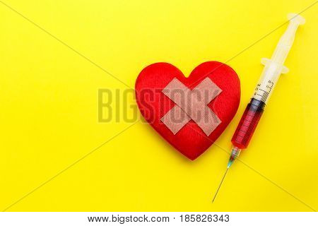 Syringe Give Medicine To Red Heart Shape On Yellow Background. Use For Heart Problem Or Illness Conc