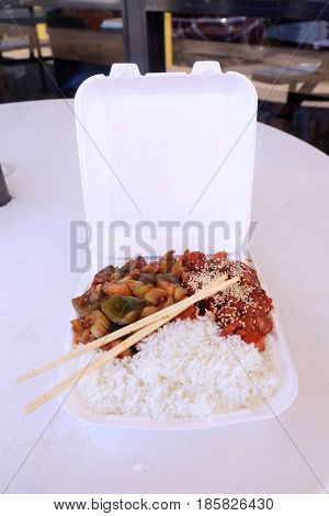 Chinese fast food outside in a foam to go container on a table.