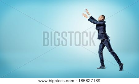 A businessman in side view with both hands raised up trying to catch something above. Loss of fortune. Grab your luck. Catching fortune.