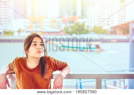 Beautiful biracial teen girl resting arms on railing by the riverside with sunny boat and urban scene in background