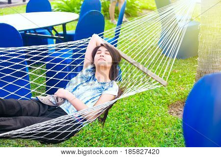 Beautiful biracial teen girl resting in large hammock at tropical resort with eyes closed relaxing