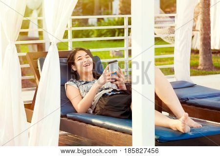 Beautiful biracial teen girl using smartphone while relaxing on lounger at resort