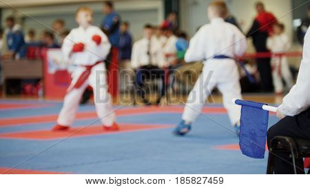 De-focused martial art competitions- karate - judge coaches looking at female teenager's karate fighting, close up