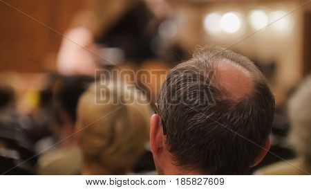 Spectators at concert - bald man is watching theatrical performance, telephoto
