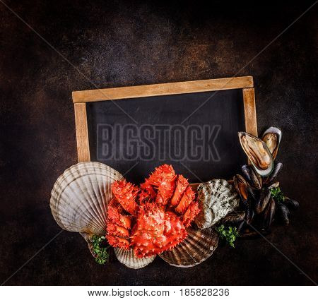 Seafood cuisine plate as an ocean gourmet dinner background with copy spase. Crab, seashells, oysters, shrimp and other seafood delicacies.