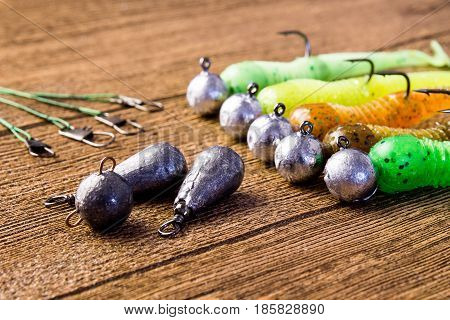 jig fishing lures on a brown wooden background