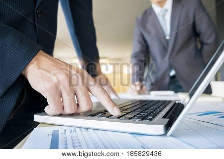 Closeup Of Businessman Is Keyboarding On Portable Net-book, While Is Sitting In Modern Office Interi