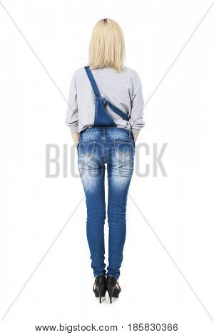 Full portrait of Stylish young blonde woman in blue denim overalls and black shoes, isolated on white background