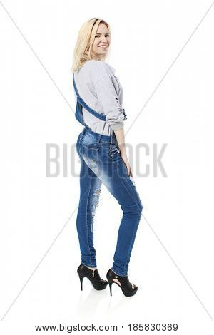 Full portrait of Stylish young blonde woman in blue denim overalls and black shoes, isolated on white background. The inscription on the T-shirt - TO BE COOL