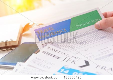 Airline boarding pass tickets in hand with travel insurance, sunglasses, pen and notebook as a concept of traveling