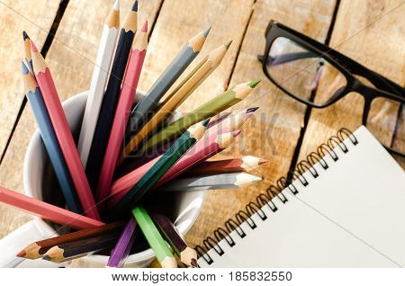 Notebooks pencils Equipment on the wooden floor with the morning sun shining faintly.