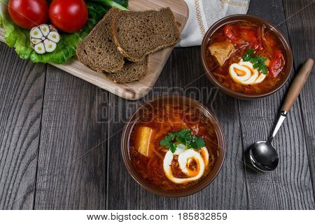 Tomato soup . Traditional  Ukrainian beetroot and tomato soup - borsch in clay pot with sour cream, garlic, herbs and bread on dark wooden background.Ingredients on table