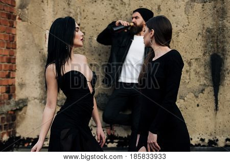 pretty girls with long brunette hair in fashion black dresses watching brutal man with beard drinking wine from bottle on blurred grungy cement wall. Unhealthy habits and lifestyle