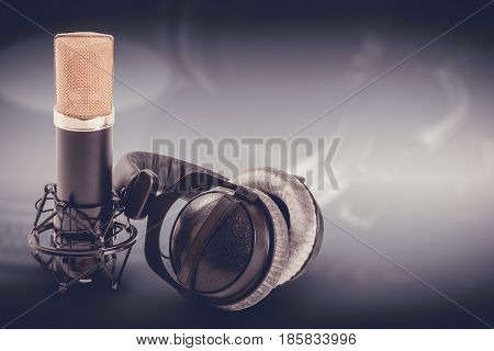 Headphones and condenser microphone on the dark background.