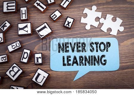 Never stop learning concept. Speech Bubble on a dark textured wooden background.