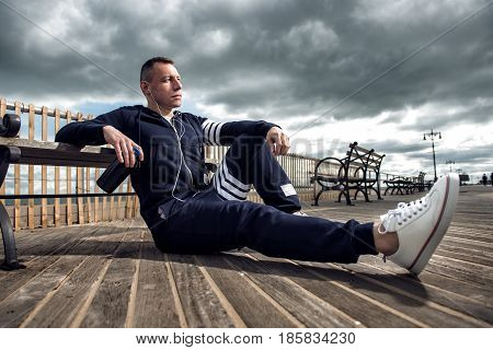 Adult man resting after the run sitting outdoors drinking protein and listen music