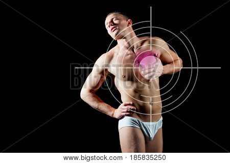 heartache. man suffers from heartache standing over black background A guy with bare body and muscular torso in white pants. Concept with Healthcare And Medicine.